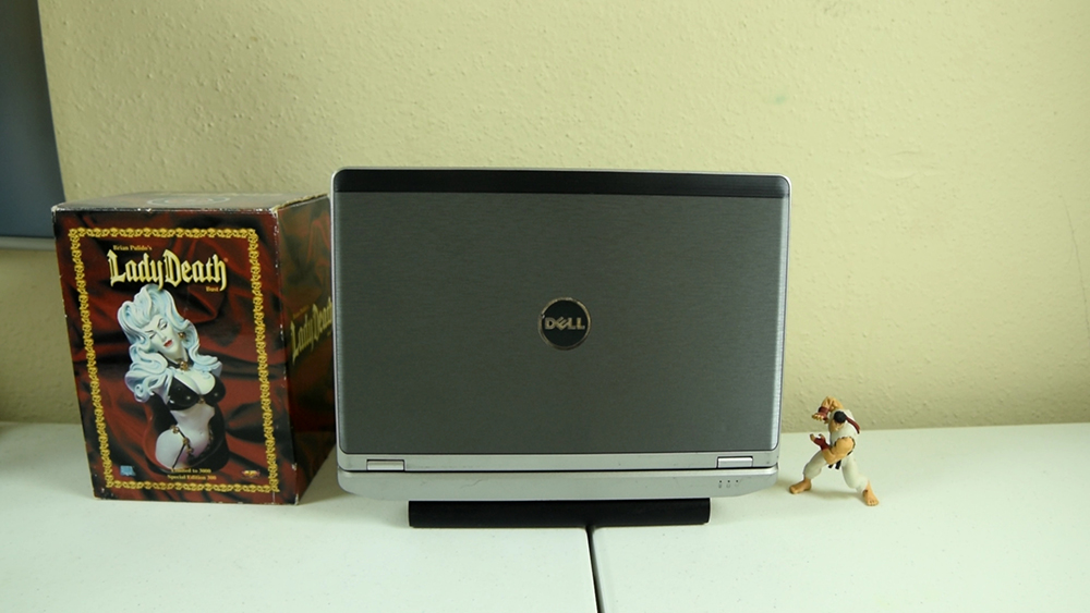 Picture of the Dell Latitude E6230 standing closed straight up so the dell logo on the hood is facing you