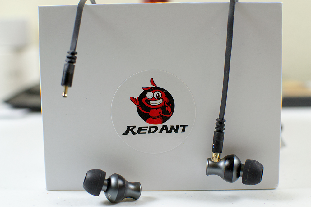 Picture of the RedAnt G2 earbuds hanging over it's product box that has a cartoonish picture of a red ant on it as the company branding